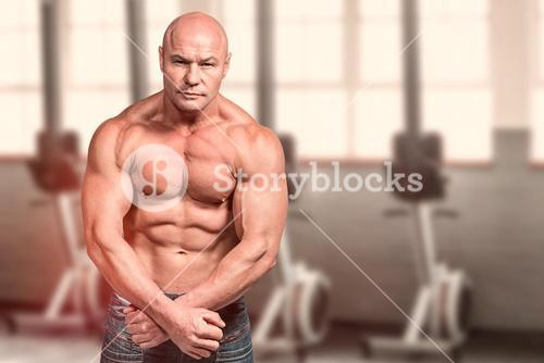 Composite image of portrait of bald man flexing muscles
