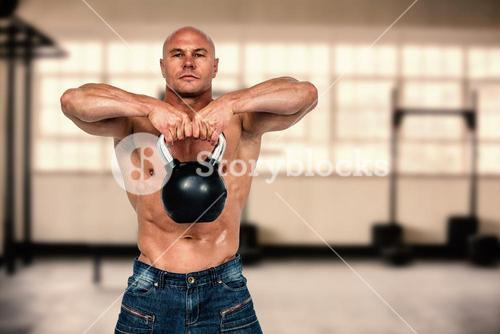 Composite image of portrait of bald man exercising with kettlebell