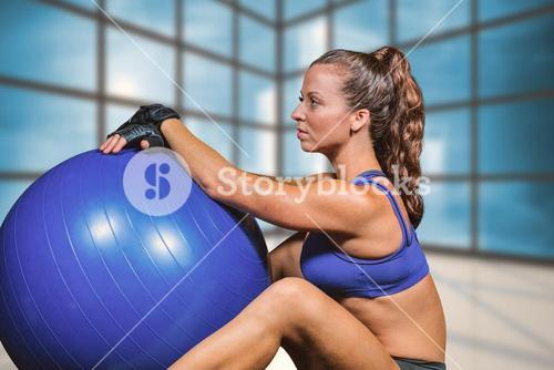 Composite image of side view of sporty woman with exercise ball