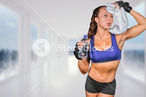 Composite image of exhausted woman wiping sweat while holding water bottle
