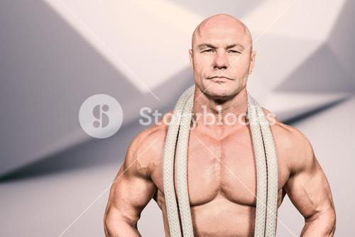 Composite image of portrait of confident fit man with rope around neck