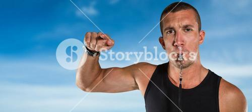 Composite image of portrait of attentive trainer blowing his whistle
