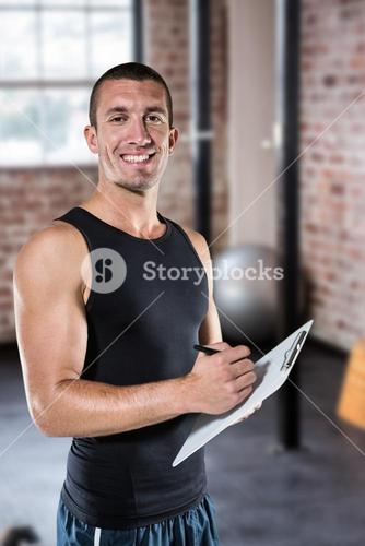 Composite image of smiling sports coach writing on clipboard