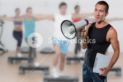 Composite image of trainer using megaphone while holding clipboard