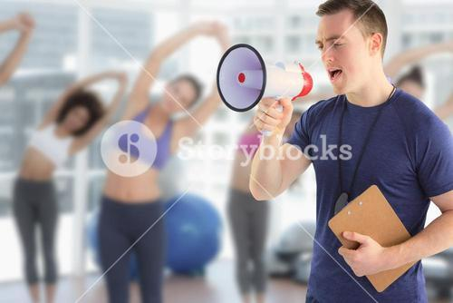 Composite image of male trainer yelling through the megaphone