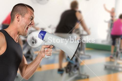 Composite image of irritated male trainer yelling through megaphone