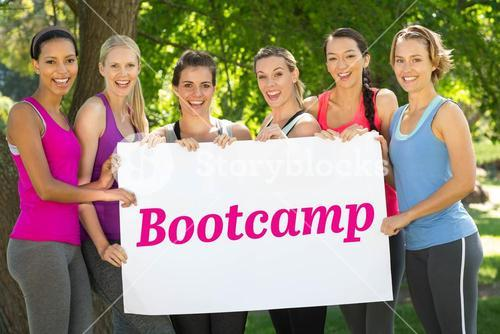 Bootcamp against fitness group holding poster in park