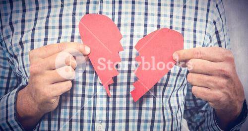 Composite image of sad man with broken heart