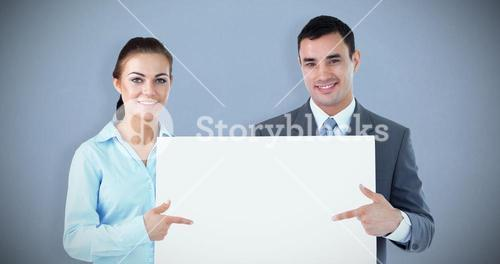 Composite image of business partners presenting sign together