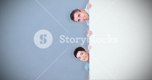 Composite image of woman and man hiding behind a blank panel