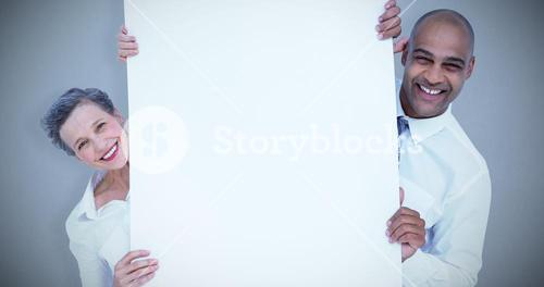 Composite image of business people holding blank sign