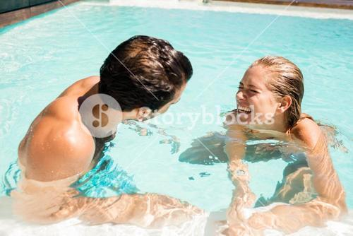 Happy couple laughing in the pool