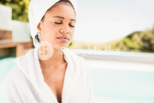 Peaceful brunette with closed eyes wearing white towel