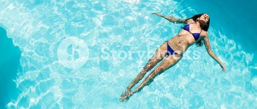 Calm woman floating in the pool