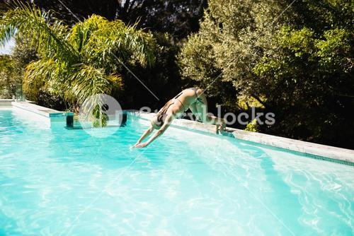 Fit blonde diving in the pool