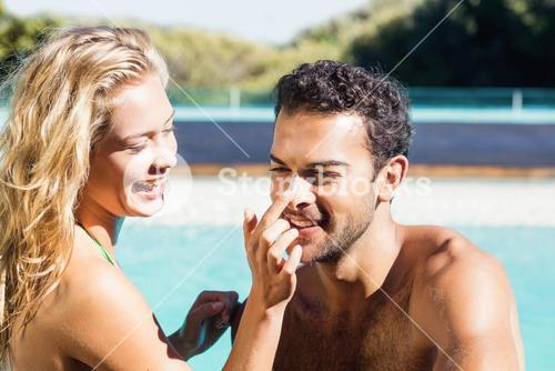 Girlfriend applying cream to boyfriend