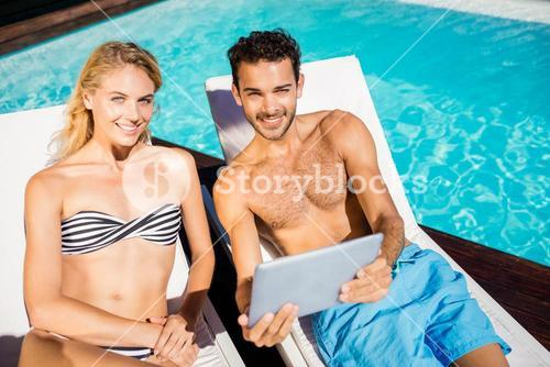 Couple using tablet on deckchairs