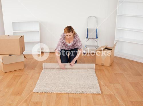 Blonde woman rolling up a carpet to prepare to move house