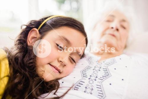 Relaxed granddaughter and grandmother napping