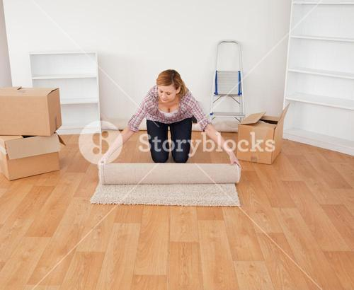 Blondhaired woman rolling up a carpet to prepare to move house