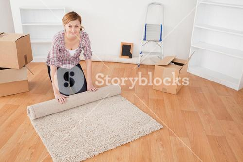 Attractive woman rolling up a carpet to prepare to move house