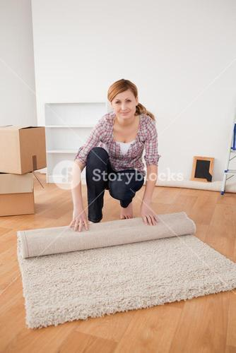 Young woman rolling up a carpet to prepare to move house