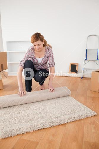 Pretty woman rolling up a carpet to prepare to move house