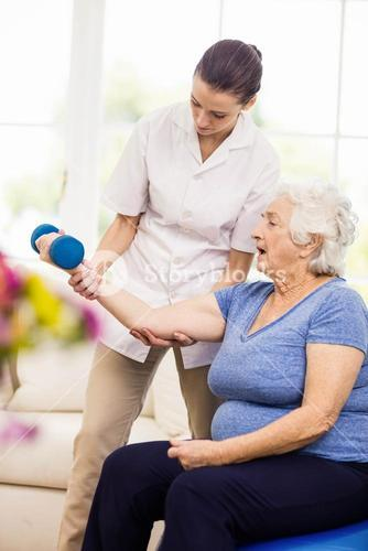 Physiotherapist taking care of sick elderly patient