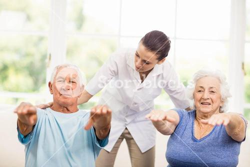 Physiotherapist taking care of sick elderly patients