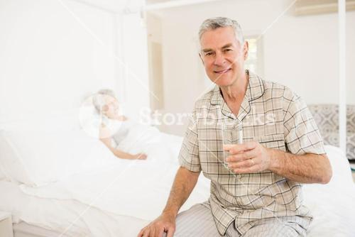Peaceful senior man holding glass of water