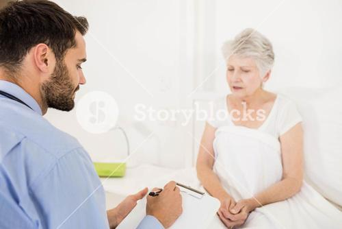 Home nurse listening to elderly woman and writing on clipboard