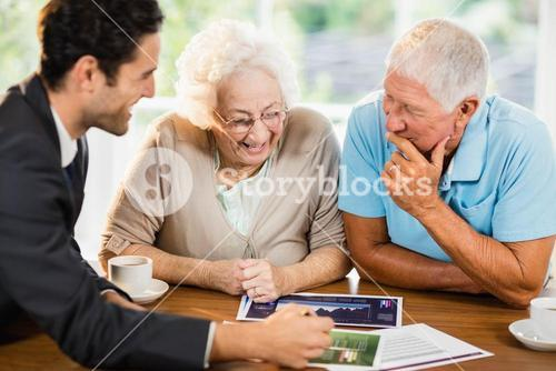 Businessman showing sheets to senior couple