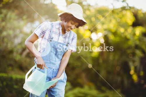Smiling woman watering plants
