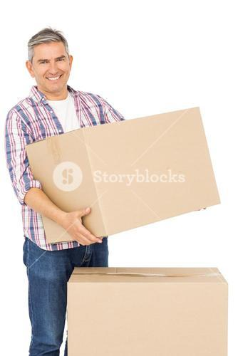 Happy man posing with moving boxes
