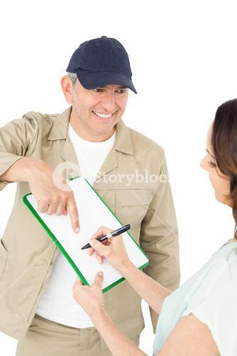 Female customer signing on paper with delivery man