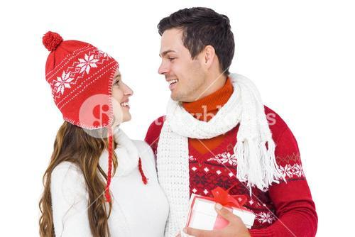 Happy couple with winter clothes holding gift box