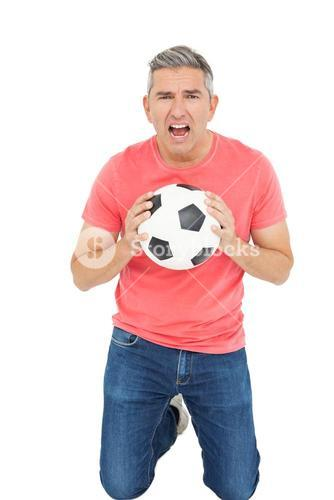 Man shouting and holding a soccer ball