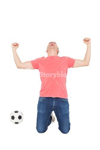 Excited man shouting with fist up and a soccer ball