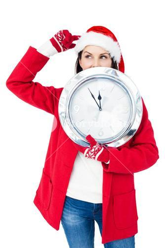 Beautiful brunette with santa hat holding a clock