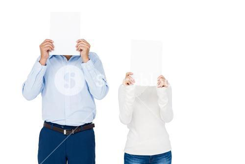 Couple covering face with paper