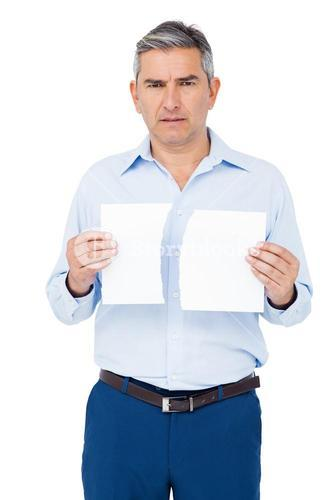 Stern man holding ripped paper