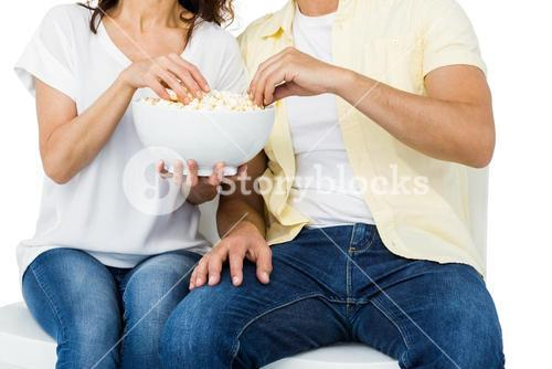 Smiling couple eating popcorn