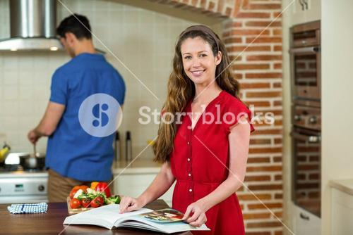 Woman checking the recipe book and man cooking on stove
