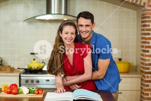 Couple embracing while checking the recipe book