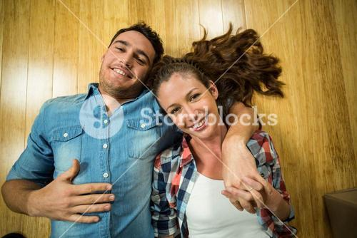 Young couple lying on floor in their house