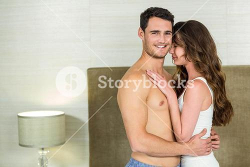 Young couple embracing in bedroom