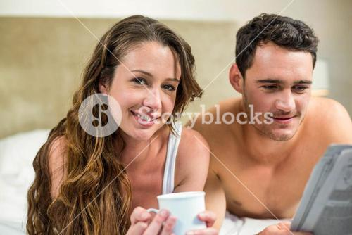 Young couple reading newspaper on bed