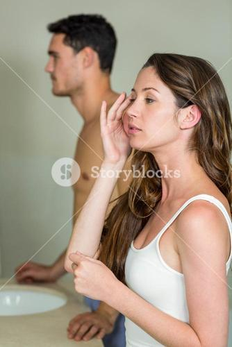 Couple looking in bathroom mirror