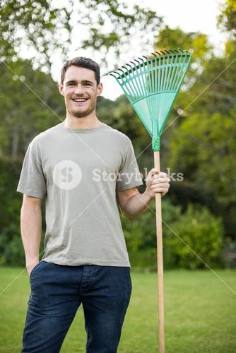 Portrait of young man standing with a gardening rake