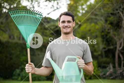 Portrait of young man standing with a gardening rake and watering can